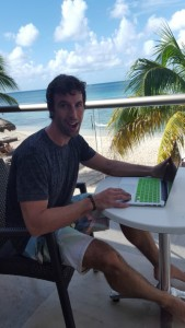 kyle on deck with computer with beach