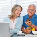 Senior man showing mobile phone to female