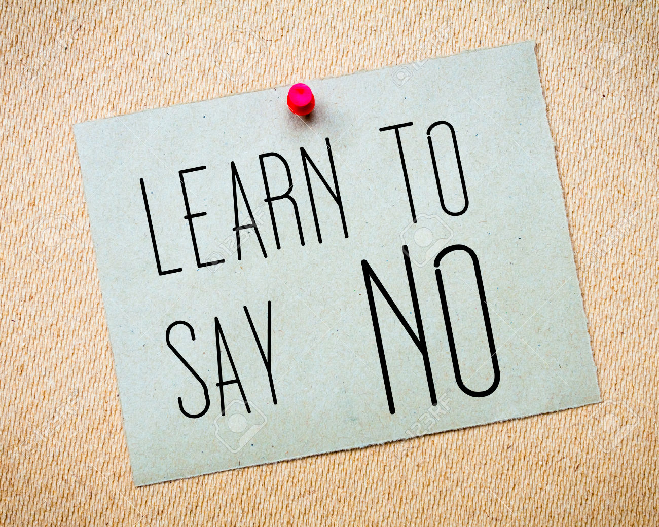 Recycled paper note pinned on cork board. Learn to say NO Message. Concept Image